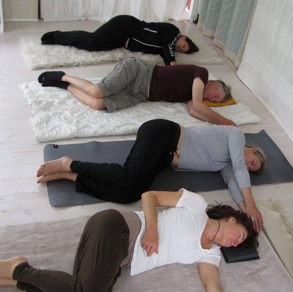 fire personer, der ligger på gulv og laver søvnøvelse