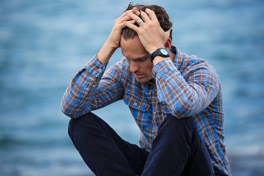 stresset mand sidder med hovedet bøjet ned i hænderne