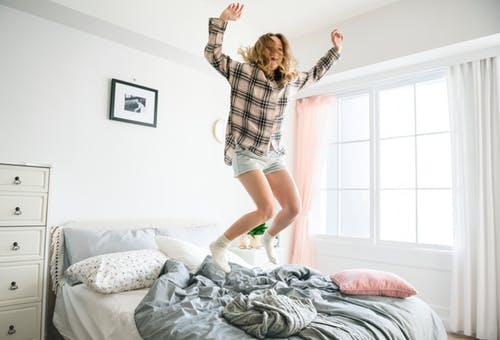 kvinde, der hopper glad i sin seng