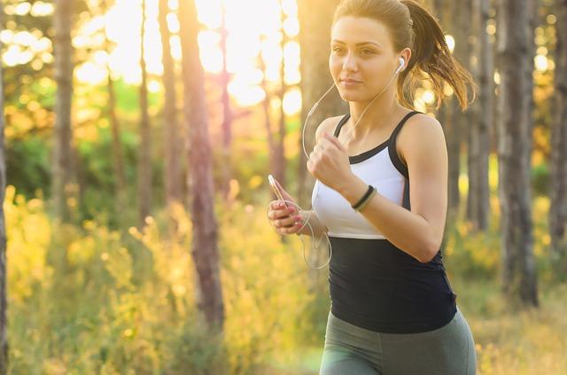 kvinde der løber i solbeskinnet skov