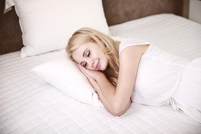 smilende kvinde i seng